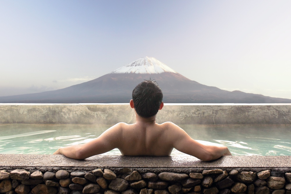 Asian man relaxing in outdoor Japanese bath with Mt. Fuji view