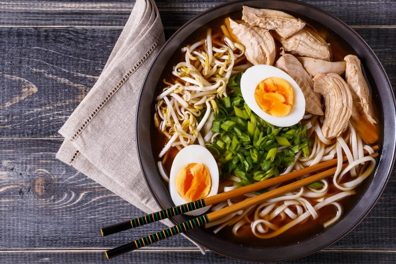 Japanese ramen soup with chicken, egg, chives and sprout on dark wooden background