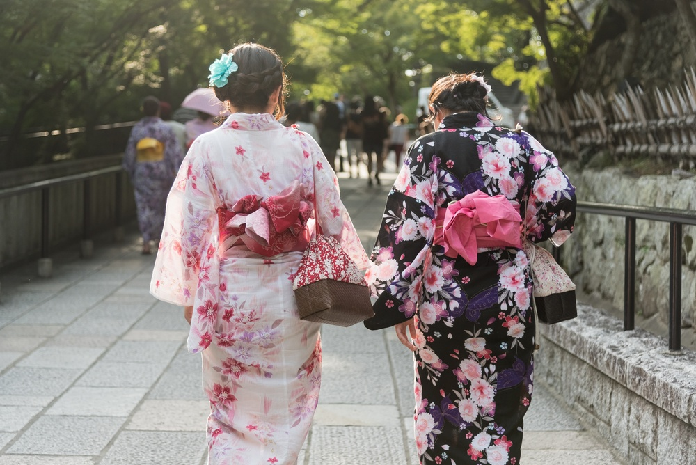 Two Japanese Women Wearing Kinomo Costume walking on the Cobble Stone Walkway in the Temple in Kyoto