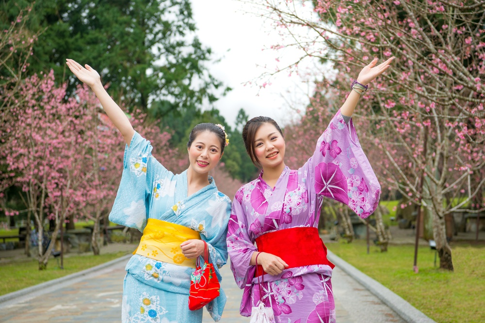 Happy freedom two women open arms with cherry-blossom sanctuary outdoors. Carefree japanese girls sightseeing sakura and dress beauty kimono during april vacation in japan.